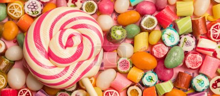 Photo for Panoramic shot of bright round lollipop on wooden stick near fruit caramel candies on pink background - Royalty Free Image