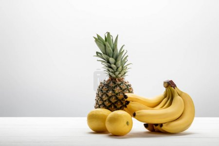 Photo for Ripe yellow bananas near sweet pineapple and lemons on white - Royalty Free Image