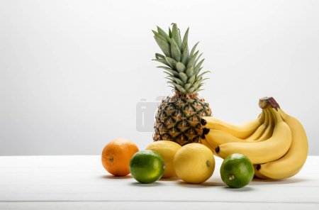 Photo for Ripe bananas near sweet pineapple, lemons, orange and limes on white - Royalty Free Image