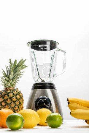 Photo pour Vue à faible angle du mélangeur près des bananes jaunes, ananas mûrs, citrons, orange et limes sur blanc - image libre de droit