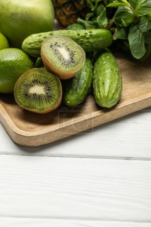 Photo for Halves of tasty ripe kiwi fruit near cucumbers on wooden cutting board - Royalty Free Image