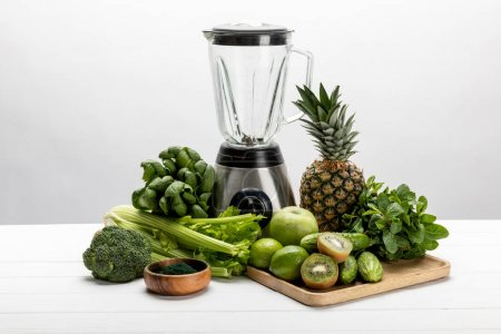 Photo for Blender near green fresh vegetables and tasty fruits on white - Royalty Free Image