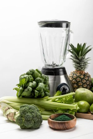 Photo for Blender near fresh, green vegetables and organic fruits on white - Royalty Free Image