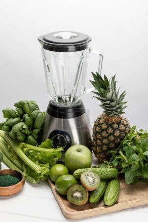 Photo for Blender near green, fresh vegetables and organic raw fruits on white - Royalty Free Image