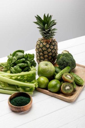 Photo pour Fruits frais savoureux près des légumes biologiques et crus sur le gris - image libre de droit