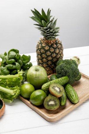 Foto de Tasty fresh pineapple, apple and limes near organic and raw vegetables on grey - Imagen libre de derechos