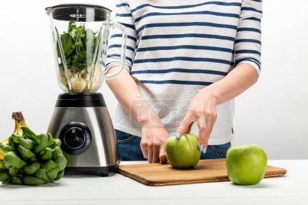 Photo pour Vue recadrée de femme coupant la pomme verte près du mélangeur et des bananes sur le blanc - image libre de droit