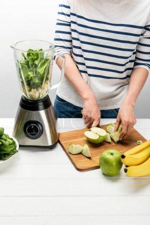 Photo pour Vue au-dessus de la pomme de coupe de femme près du mélangeur et des bananes sur le blanc - image libre de droit