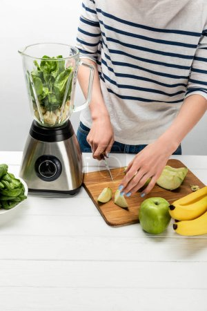 Photo for Cropped view of woman cutting organic apple near blender with ingredients on white - Royalty Free Image