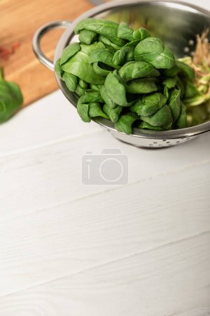 Photo for Fresh green and organic spinach leaves in colander on white surface - Royalty Free Image