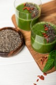 "Постер, картина, фотообои ""tasty green smoothie in glasses with chia seeds and goji berries on white surface """