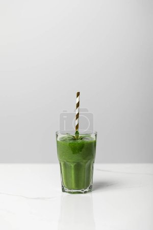 Photo for Tasty, green and organic smoothie in glass with straw on grey - Royalty Free Image