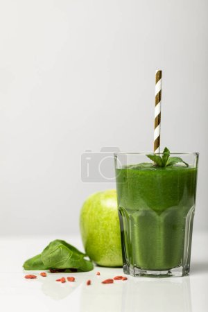 Photo for Green smoothie in glass with straw near ripe organic apple on grey - Royalty Free Image