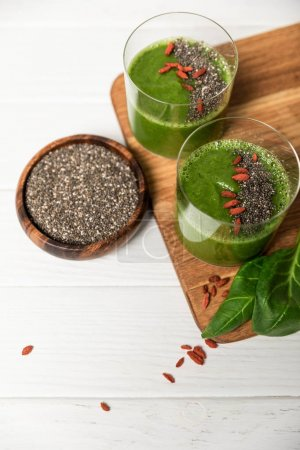 Photo for Top view of chia seeds in bowl near glasses of green smoothie on white - Royalty Free Image