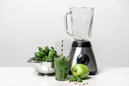 Photo for Tasty green smoothie in glass with straw near fresh spinach leaves, apple and blender on white - Royalty Free Image