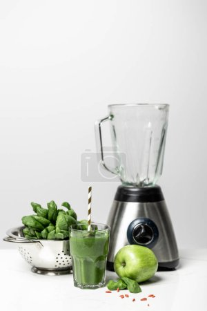 Photo for Tasty smoothie in glass with straw near fresh spinach leaves, apple and blender on white - Royalty Free Image