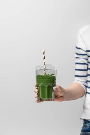 Photo for Cropped view of woman holding glass with tasty green smoothie and straw on white - Royalty Free Image