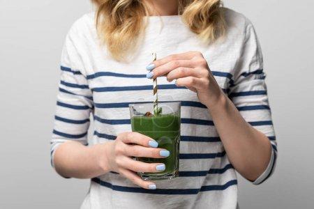 Photo pour Vue recadrée de la femme tenant paille et verre avec smoothie vert savoureux sur blanc - image libre de droit
