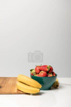 Foto de Fresas dulces en un tazón cerca de plátanos amarillos y tabla de cortar en gris - Imagen libre de derechos