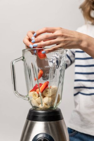 Photo for Cropped view of woman putting red strawberries in blender with bananas on white - Royalty Free Image