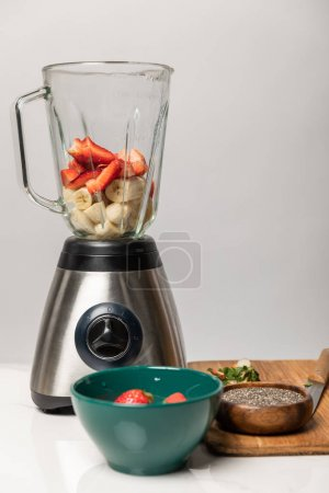 Photo for Sweet strawberries and ripe bananas in blender near bowls and cutting board on grey - Royalty Free Image
