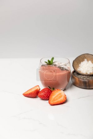 Photo for Tasty smoothie with coconut flakes in glass near tasty strawberries on grey - Royalty Free Image