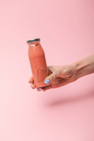Photo for Cropped view of woman holding glass bottle with tasty smoothie on pink - Royalty Free Image