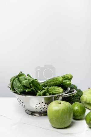 Photo for Green apple near tasty vegetables and spinach leaves on white - Royalty Free Image