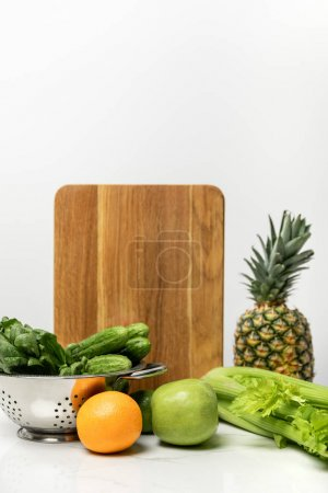 Foto de Ripe fruits near fresh vegetables and wooden cutting board on white - Imagen libre de derechos