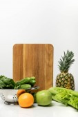 "Постер, картина, фотообои ""ripe fruits near fresh vegetables and wooden cutting board on white """