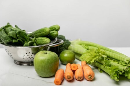 Photo for Sweet carrots near ripe apple and green vegetables on grey - Royalty Free Image