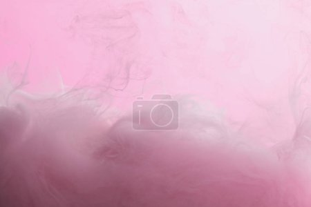 Close up view of pink paint mixing in water isolated on pink