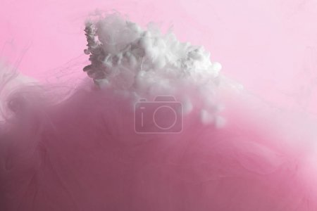 Photo for Close up view of white and pink paint mixing in water isolated on pink - Royalty Free Image