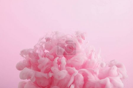Photo pour Fermez-vous vers le haut de la vue des tourbillons roses de peinture dans l'eau d'isolement sur le rose - image libre de droit