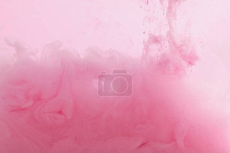 Photo for Close up view of pink paint mixing in water - Royalty Free Image