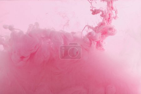 Close up view of pink paint swirls mixing in water