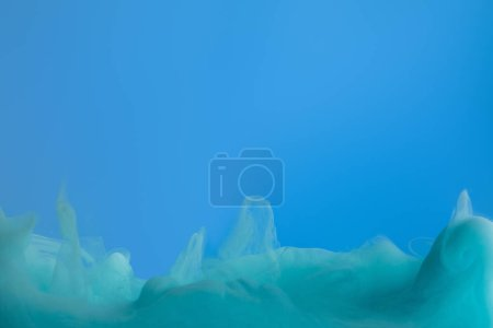 Close up view of turquoise paint swirls isolated on blue