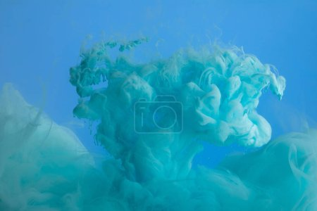Photo for Close up view of turquoise paint swirls isolated on blue - Royalty Free Image