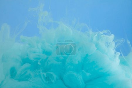Photo for Close up view of turquoise watercolor paint swirls isolated on blue - Royalty Free Image