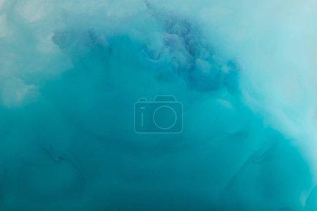 Foto de Close up view of turquoise watercolor swirls in water - Imagen libre de derechos