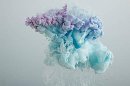 Nahaufnahme von hellblauen, rosa und lila Farbmischungen isoliert auf grau