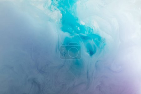 Foto de Close up view of blue and purple smoky paint swirls in water - Imagen libre de derechos