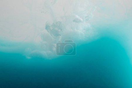 Photo pour Vue rapprochée des tourbillons de peinture blanche et bleue dans l'eau - image libre de droit