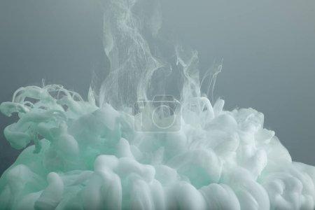 Photo pour Fermez-vous vers le haut de la vue des tourbillons verts légers de peinture d'isolement sur le gris - image libre de droit