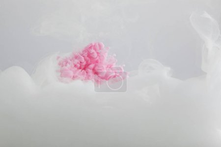 Photo for Close up view of pink and white paint mixing isolated on grey - Royalty Free Image