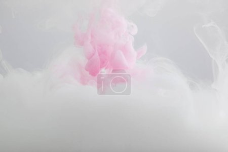 Foto de Close up view of pink and white paint mixing isolated on grey - Imagen libre de derechos