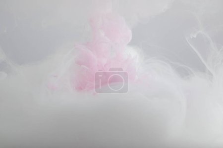 Photo for Close up view of pink and white paint mixing in water - Royalty Free Image