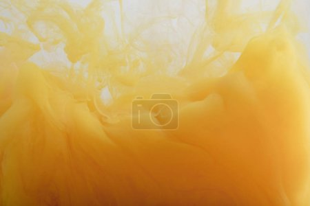 Photo for Close up view of light orange paint mixing in water - Royalty Free Image