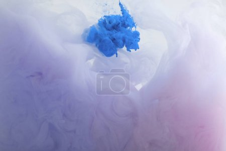 Close up view of blue and purple watercolor paint swirls in water