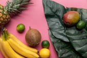 "Постер, картина, фотообои ""whole ripe tropical fruits with green leaves on pink background"""